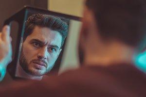 Evil guy looks in the mirror.