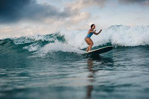 Young woman in bright bikini surfing on a board in ocean