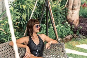 Beautiful woman in sunglasses relaxing in chaise-longue on sun bed sofa lounge chair on holidays. Summer luxury vacation. Bali island.