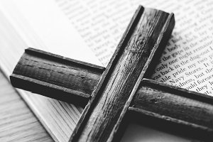 Closeup of wooden cross on bible