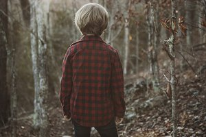 Boy Standing on a Rock in the Woods