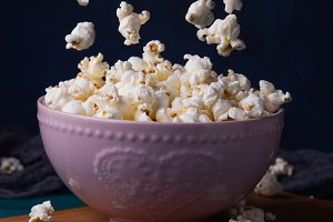 Popcorn in pink bowl on dark backgro
