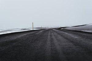 Dark Road through Snowy Landscape