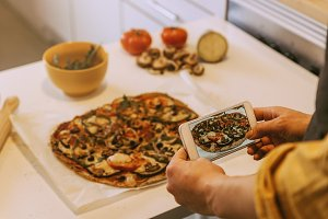 Woman taking picture to pizza.