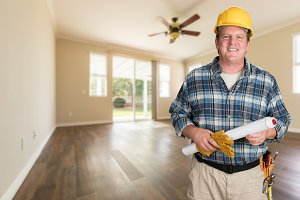 Contractor With Plans In Empty Room