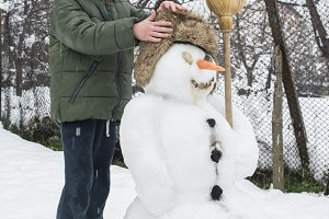 Snowman and child in the yard