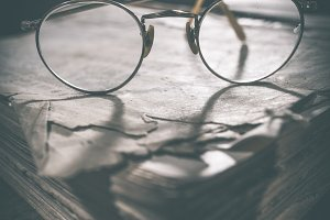 Old vintage round glasses and book
