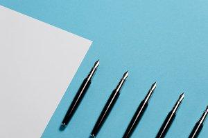Black pen lies on a clean white shee