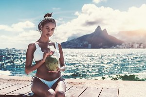 Black girl in swimsuit with coconut