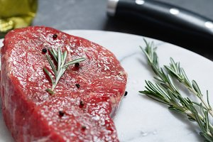 Raw beef steak on a white marble