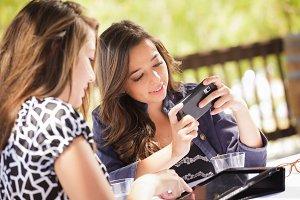 Two Women Using Electronics