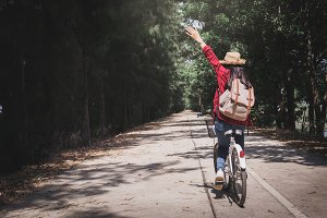 woman backpacker with white bicycle