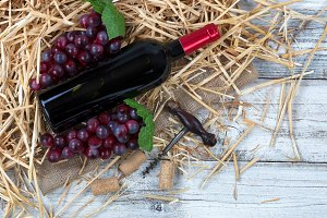 Red wines and grapes on straw