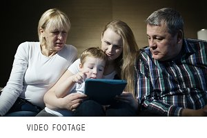 Family watching boy playing game
