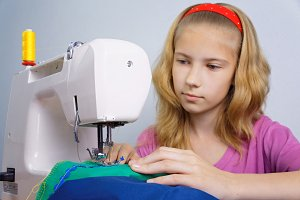 Girl learns to sew on an electric se
