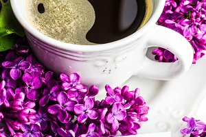 Coffee time with lilac flowers