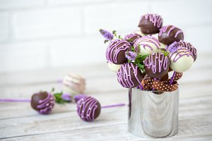Colorful cake pops on a white wall