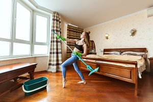 Woman is dancing with a mop.