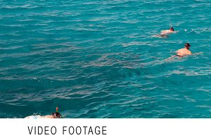 Group of people swimming on open sea