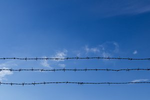 Barbed wire and blue sky with clouds