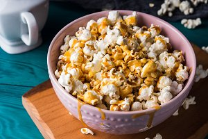 Popcorn with caramel in bowl on dark