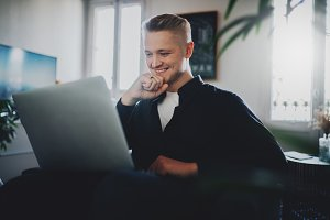 Handsome smiling man using laptop