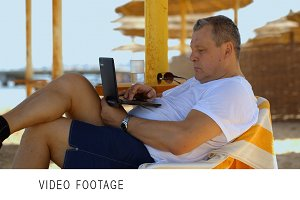 Man relaxing with a laptop at beach