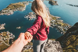 Couple follow holding hands on cliff