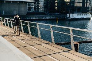 Woman Riding Bike over Bridge