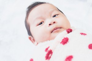 Cute little baby on a white cloth.