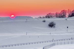 Sunset over snowed landscape