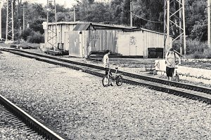 Guys with bicycles on railroad b&w