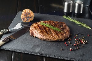 Grilled beef steak on stone plate ov