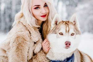 Blonde in a fur coat with her dog