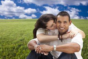 Hispanic Couple Sitting in Grass