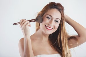 Smiling woman applying make up