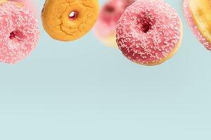Falling pink glazed doughnuts