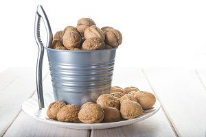 Bucket full of walnuts with a nutcra