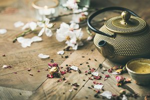 Iron teapot, cups, dried rose buds