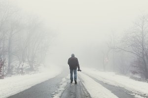 Nature photographer on foggy road