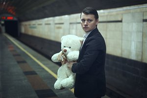 Sad young man with a teddy bear.