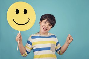 A kid holding a happy emoticon face