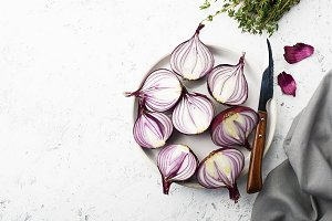 Red sweet onions halves on a white p