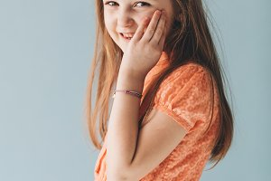Carefree young girl in a cute orange