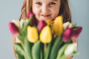 Little girl giving colorful flowers,