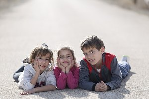 Three children lying on the ground