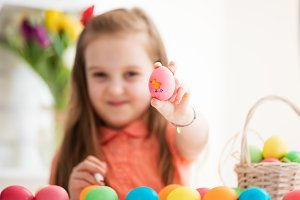 Young girl showing drawing on an egg
