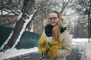 Girl in a snowy city with a bouquet