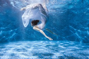 Woman in a dress under the water.