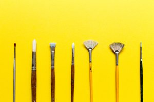 Paintbrushes on yellow background
